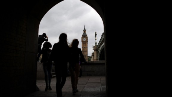 Pedestrians walk along the South Bank opposite the Big Ben clock face and the Elizabeth Tower at Houses of Parliament in central London on June 29, 2016.