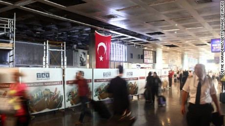 Passengers walk in the damaged parts of the international terminal of the country's largest airport, Istanbul Ataturk, following yesterday's blast on June 29, 2016 in Istanbul, Turkey.