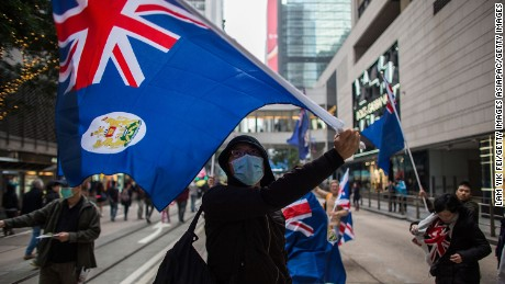 Pro-democracy protesters wave the flag of colonial Hong Kong during a march for democracy on February 1, 2015.