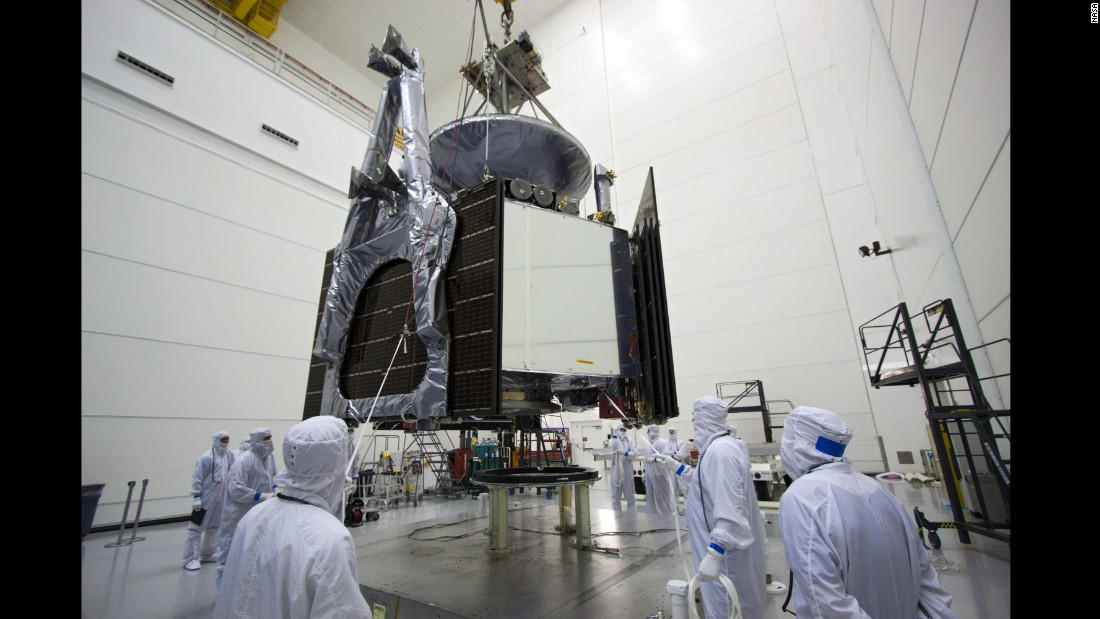 Technicians use a crane to lower Juno onto a stand where the spacecraft was loaded with fuel for its mission.