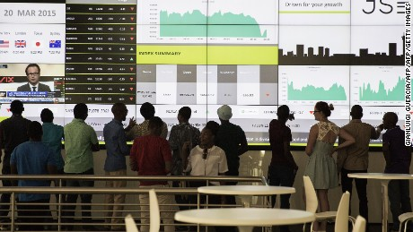 People from a school group look at an electronic screen with stock index figures at the Johannesburg Stock Exchange (JSE) on March 20, 2015 in Johannesburg, South Africa. AFP PHOTO/GIANLUIGI GUERCIA        (Photo credit should read GIANLUIGI GUERCIA/AFP/Getty Images)