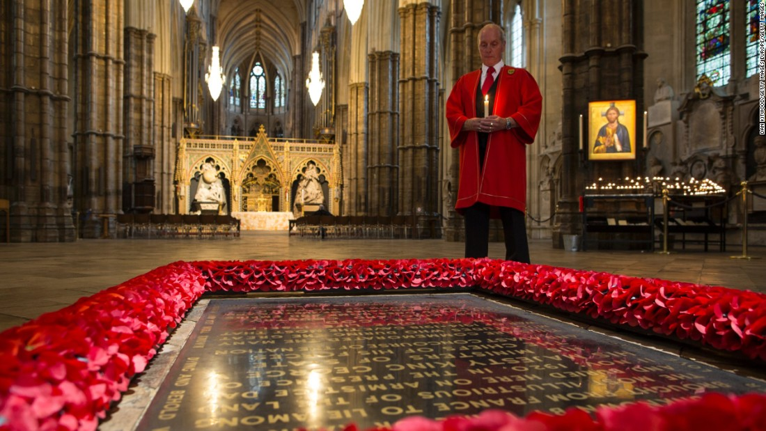 "An abbey marshal poses next to ""The Grave of the Unknown Warrior"" in London's Westminster Abbey."