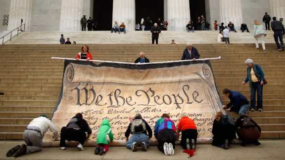 Volunteers help roll up a giant banner printed with the Preamble to the United States Constitution during a demonstration against the Supreme Court's Citizens United ruling at the Lincoln Memorial on the National Mall October 20, 2010 in Washington, DC.