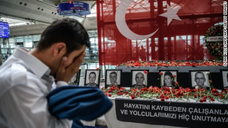 An airport employee mourns for his collegues as he looks at the pictures of killed airport employees at Ataturk airport international terminal in Istanbul on June 30, 2016 two days after the triple suicide bombing and gun attack occurred at Istanbul's Ataturk airport. The death toll from the triple suicide bombing and gun attack that occurred on June 28, 2016 at Istanbul's Ataturk airport has risen to 43 including 19 foreigners. The government has pointed the finger of blame at the Islamic State group and Turkish police rounded up 13 suspected IS jihadists in raids at 16 different locations across Istanbul on June 30. / AFP / OZAN KOSE        (Photo credit should read OZAN KOSE/AFP/Getty Images)