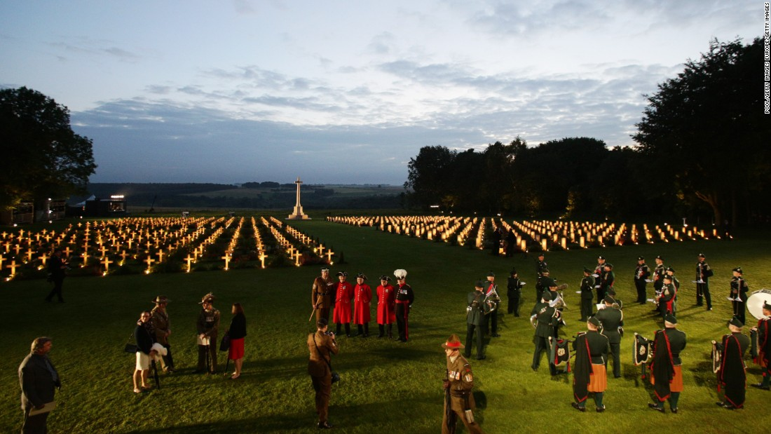 Attendees are seen among the illuminated graves of the Thiepval Memorial to the Missing.