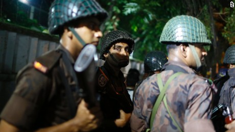 Bangladeshi security personnel stand guard near the restaurant.
