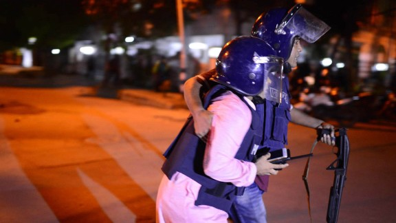 Bangladeshi police take cover near a restaurant that has been attacked by unidentified gunmen  in the early hours of July 2, 206 in Dhaka, Bangladesh. Gunmen have taken at least 20 foreigners hostage at a restaurant in the diplomatic area of Dhaka, the capital of Bangladesh.