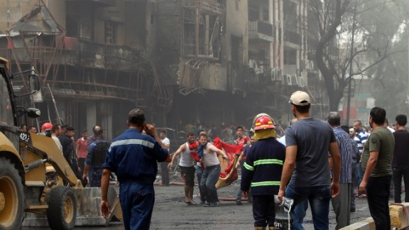 Iraqis on Sunday evacuate a body from the site of a suicide car bombing in Baghdad