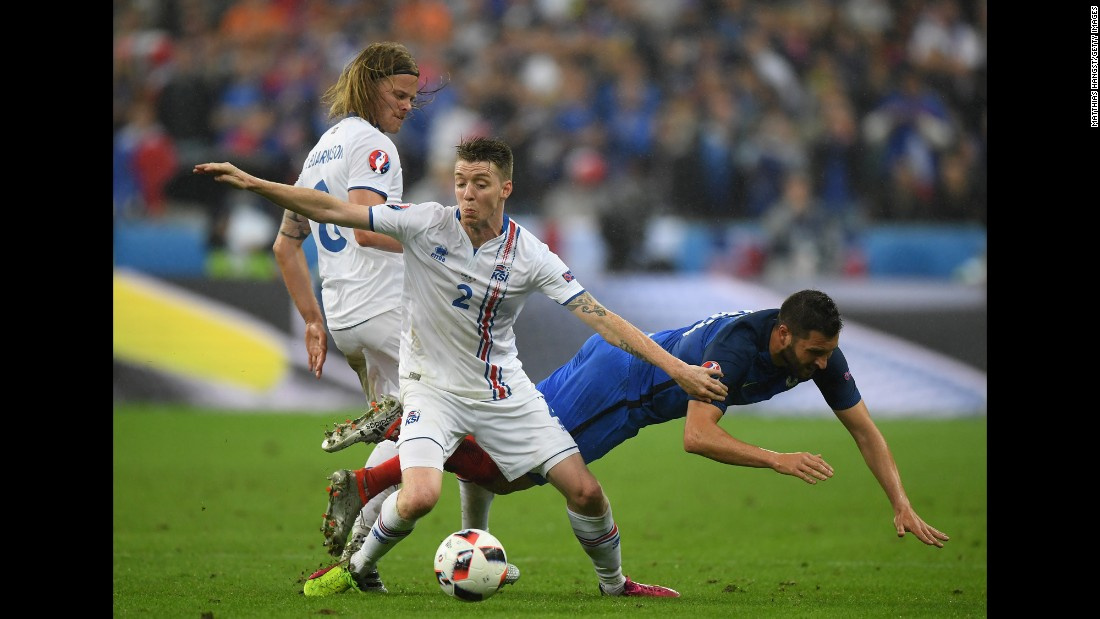 Andre-Pierre Gignac of France competes for the ball against Birkir Saevarsson and Birkir Bjarnason of Iceland.