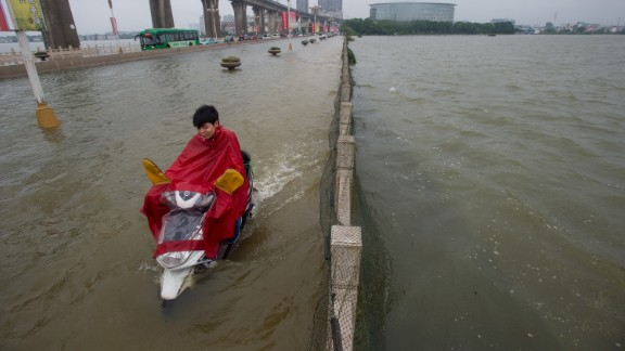 A man rides a scooter across a flooded bridge in Wuhan, July 2.