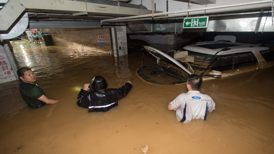 Men work to remove a car from a badly flooded parking garage in Wuhan, in China's central Hubei province on July 2, 2016.