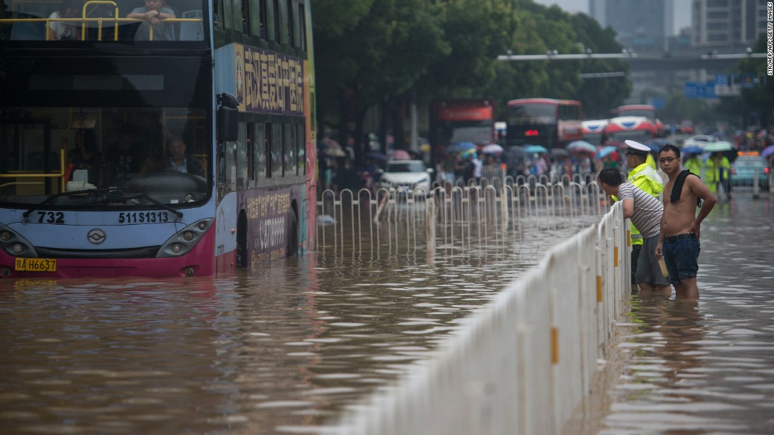People cross a flooded street in Wuhan, China.