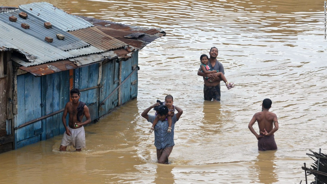 Displaced residents trudge through high flood waters following heavy monsoon rain in Dimapur on June 28, 2016.