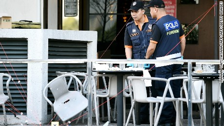 Malaysian forensic experts inspect the site of grenade attack at Movida.