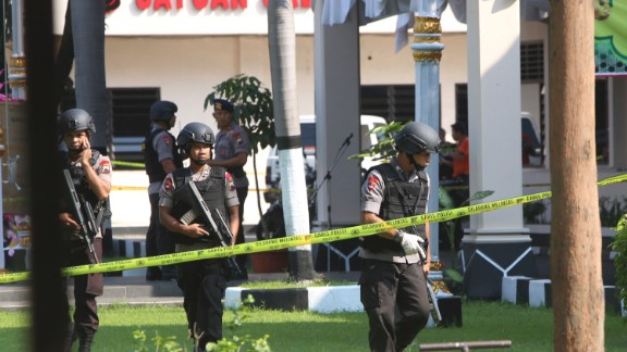Members of police bomb squad examine an area near where a suicide bomber blew himself up in Solo, Indonesia.