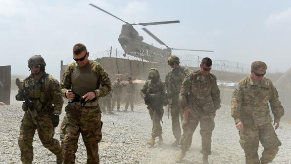 In this photograph taken on August 13, 2015, US army soldiers walk as a NATO helicopter flies overhead at coalition force Forward Operating Base (FOB) Connelly in the Khogyani district in the eastern province of Nangarhar. From his watchtower in insurgency-wracked eastern Afghanistan, US army Specialist Josh Whitten doesn