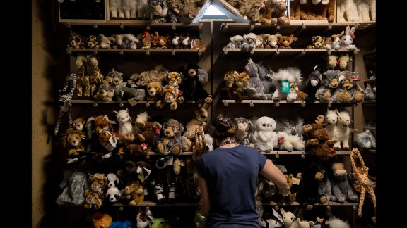 A worker puts out stuffed animals in the gift shop.