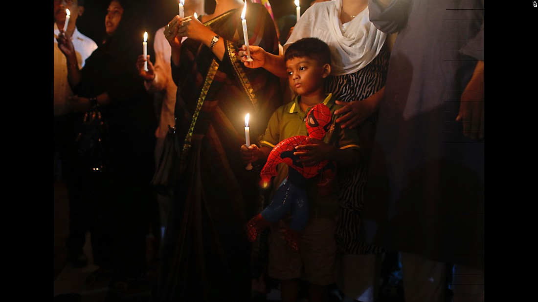"A boy holds a Spider-Man toy in one hand and a lighted candle in the other during a tribute Sunday, July 3, for those killed in a <a href=""http://www.cnn.com/2016/07/03/asia/bangladesh-dhaka-shooting/index.html"" target=""_blank"">terrorist attack</a> in Dhaka, Bangladesh. Gunmen killed 21 hostages and two police officers before authorities raided a cafe and ended the standoff."
