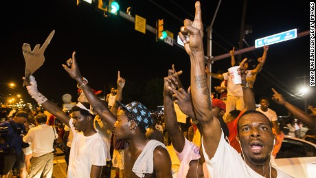 Protesters block traffic and dance on cars near the Triple S Food Mart in Baton Rouge.