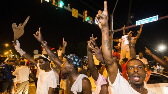 Protesters block traffic and dance on cars near the convenience store.