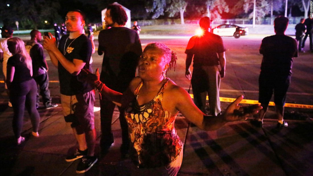 A woman joins others gathered at the scene of a police-involved shooting in Falcon Heights, Minnesota, on July 6. Philando Castile, 32, was fatally shot by police during a traffic stop. His fiancee, Diamond Reynolds, live-streamed the aftermath on Facebook. The shooting is being investigated.