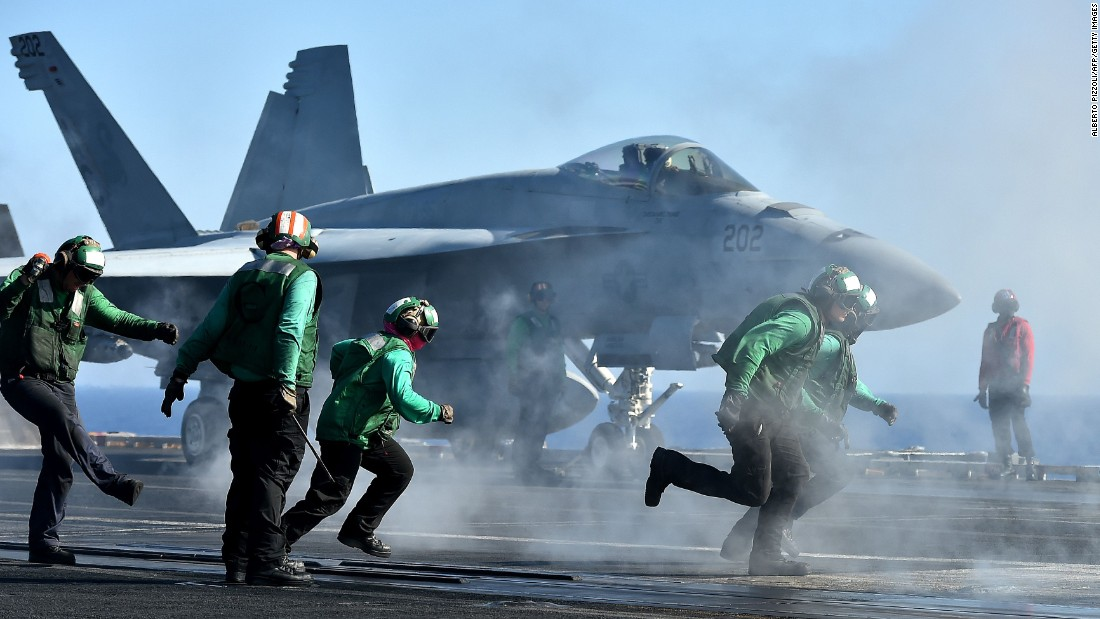 U.S. sailors run near a fighter jet on the USS Dwight D. Eisenhower on Wednesday, July 6. The aircraft carrier was in the Mediterranean Sea.