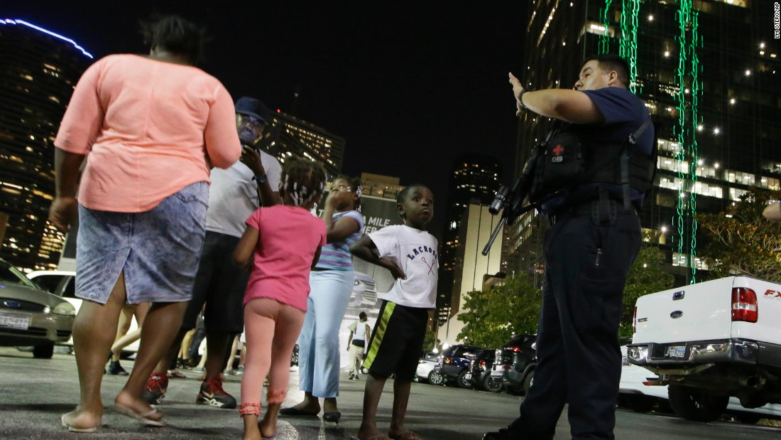 Dallas police order people away from the area after the shootings.