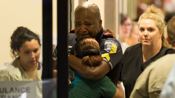 A police officer with Dallas Area Rapid Transit is comforted at the emergency room entrance of the hospital.
