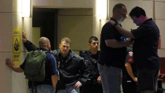 Law enforcement officials wait outside the emergency room entrance at Baylor University Medical Center.