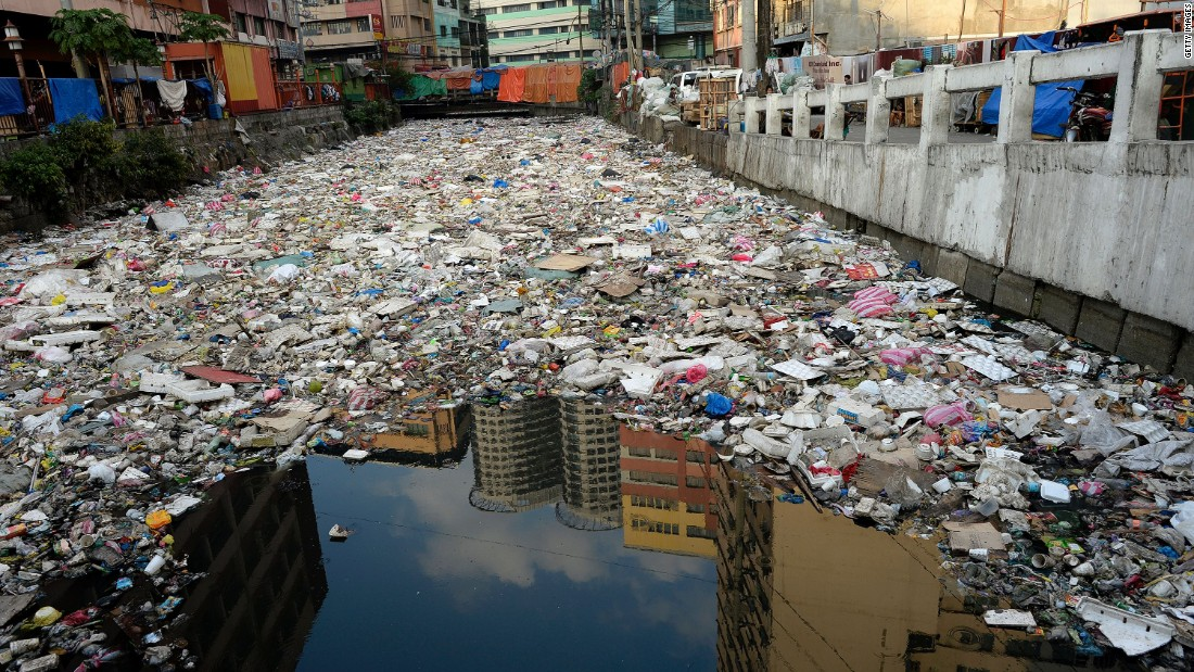 Buildings are reflected in the waters of a garbage filled river in Manila.