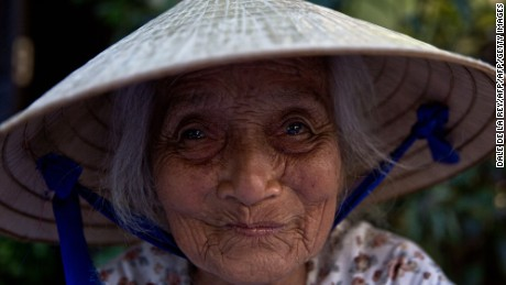 In this picture taken on June 27, 2015 an elderly woman smiles while working in a market in Hoi An, Vietnam's central Quang Nam Province. The old town area of Hoi An, a well-preserved example of a traditional Asian trading port, is recognized as a UNESCO World Heritage Site and is a popular travel destination for local and international tourists. AFP PHOTO / DALE DE LA REY        (Photo credit should read DALE de la REY/AFP/Getty Images)