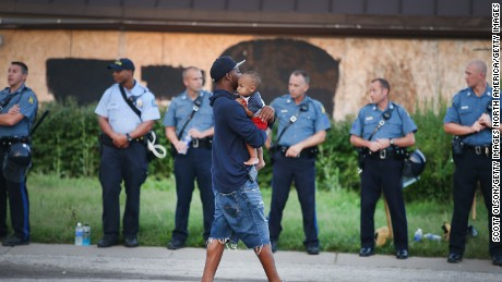 FERGUSON, MO - AUGUST 17: A man carries his child past a row of police tasked with keeping the peace as demonstration to protest the killing of teenager Michael Brown on August 17, 2014 in Ferguson, Missouri.   Despite the Brown family's continued call for peaceful demonstrations, violent protests have erupted nearly every night in Ferguson since his death. (Photo by Scott Olson/Getty Images)