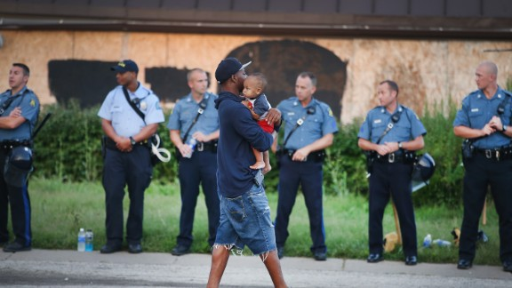 FERGUSON, MO - AUGUST 17: A man carries his child past a row of police tasked with keeping the peace as demonstration to protest the killing of teenager Michael Brown on August 17, 2014 in Ferguson, Missouri.   Despite the Brown family