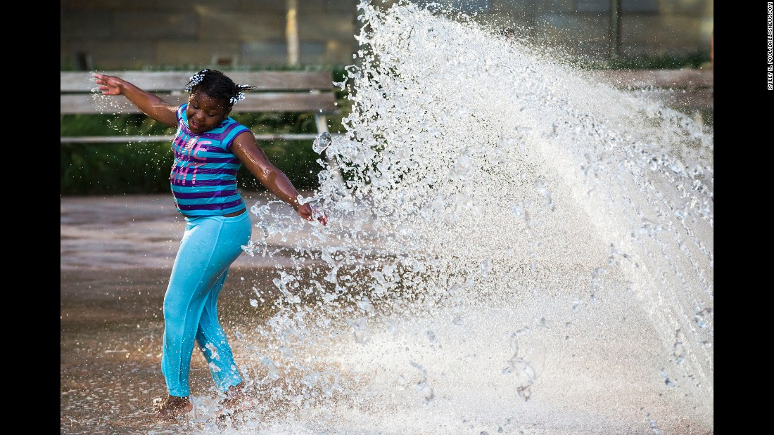 "Jonasha Wright, 8, plays in a fountain a few feet away from a protest rally. ""One of the very first photographs I was making was of a little girl spinning and twirling and smiling and laughing in a fountain in the park where the rally was. There she was, a few feet from this Black Lives Matter rally that was about to start, and she's just a little girl enjoying a summer day like every other little girl should be doing on a summer day."""