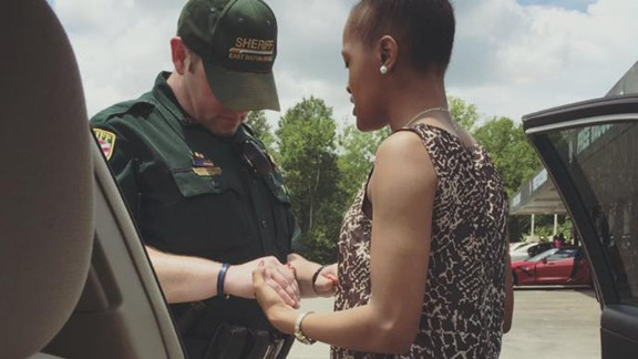 """Kim Muyaka -- head bowed, eyes closed, hands tightly entwined with those of an East Baton Rouge police officer -- prays that God would """"cover this Police Officer ... and use his hands not to hurt or harm but to protect the citizens."""" Muyaka posted this now-viral photo to her Facebook page."""