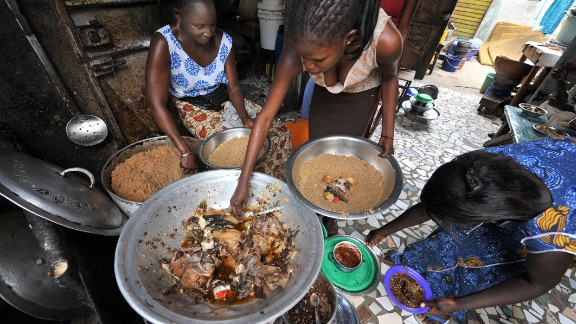 """""""As income goes up, we can consume and buy more good things, healthier things like fruits, vegetables, fresh fish, stuff like that. But we can and do also buy unhealthy things -- processed meats, sugary drinks, highly processed food,"""" Haddad says.    Pictured here, women prepare a traditional Senegalese dish of rice and fish at a street restaurant in Dakar."""