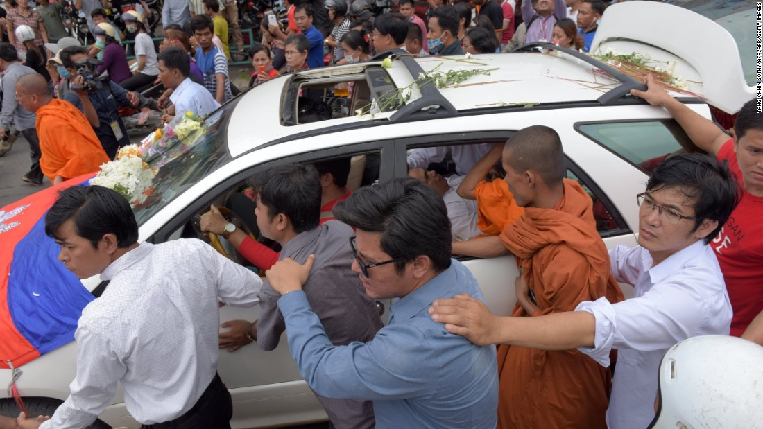 Cambodians walk along a car transporting the body of political commentator and government critic Kem Ley who was shot dead at a convenience store in Phnom Penh on July 10, 2016.