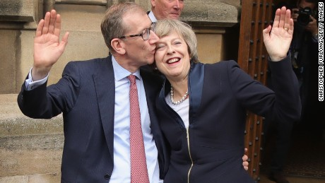 Philip May gives his wife a kiss Monday before she speaks about assuming party leadership.