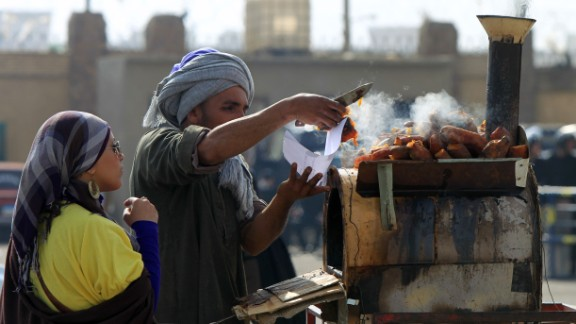 The report warns of huge health implications globally if people don't change their diets. By 2030, the number of overweight and obese people will have grown from 1.3 billion in 2005, to 3.3 billion globally -- about a third of the population, according to estimations in the report.   Pictured here, an Egyptian street vendor sells grilled sweet potatoes at a market in Cairo.