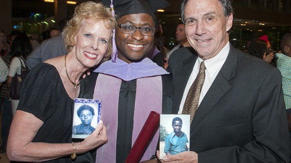 Given Kachepa at his graduation, with foster parents Sandy and Deetz Shepherd, who are holding photos of Kachepa