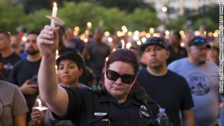 People and police officers attend a candlelight vigil for five police officers killed during anti-police brutality protests, in Dallas, Texas, on July 11, 2016.  Five officers were killed and seven others were wounded when a gunman opened fire on a  protest against recent police-involved shootings.