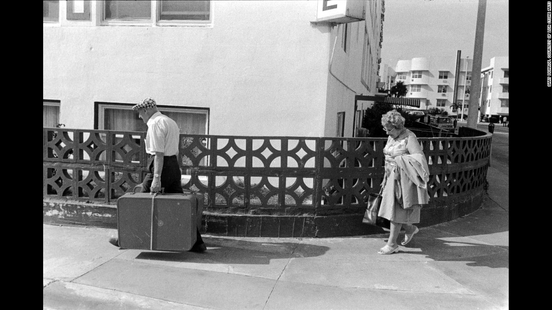 "A couple walks with their luggage at 15th Street and Ocean Drive in 1981. ""More recently I've taken to the old couple walking seemingly aimlessly across the sidewalk,"" Monroe said about this image. ""He's carrying the weight of the luggage and the world, while his wife (one assumes) walks about 10 feet behind him. It's a quiet but poignant image."""