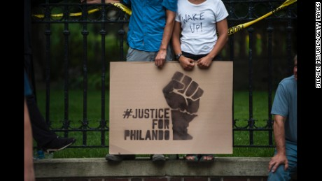 ST. PAUL, MN - JULY 07: A couple hold a sign protesting the killing of Philando Castile outside the Governor's Mansion on July 7, 2016 in St. Paul, Minnesota. Castile was shot and killed the previous night by a police officer in Falcon Heights, MN. (Photo by Stephen Maturen/Getty Images)