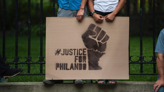 A couple hold a sign protesting the killing of Philando Castile outside the governor's mansion on July 7, in St. Paul, Minnesota. Castile's death was live-streamed by his fiancée and quickly went viral.