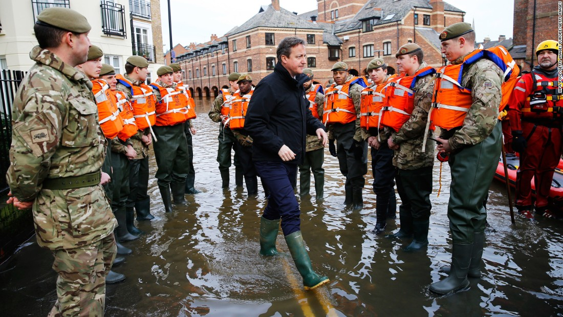 Cameron puts on a pair of wellington boots after severe flooding hit large parts of northern England in December 2015.