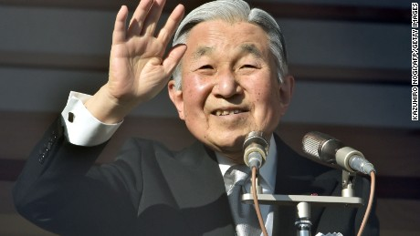Japanese Emperor Akihito waves to well-wishers gathered for the annual New Year's greetings at the Imperial Palace in Tokyo on January 2, 2016.