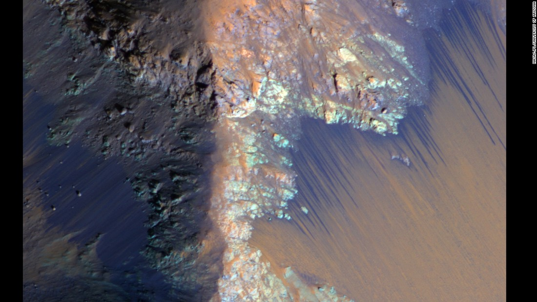 Recurring slope lineae (RSL) on Mars are seasonally abundant along the steep slopes of ancient bedrock in the Valles Marineris canyon region. Here, the RSL are depicted as bright fans that extend down the slopes. <br />