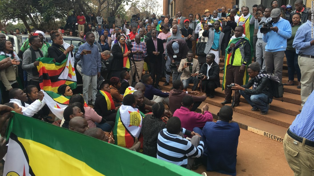 People gather draped in flags as Zimbabwean pastor Evan Mawarire appeared in court.