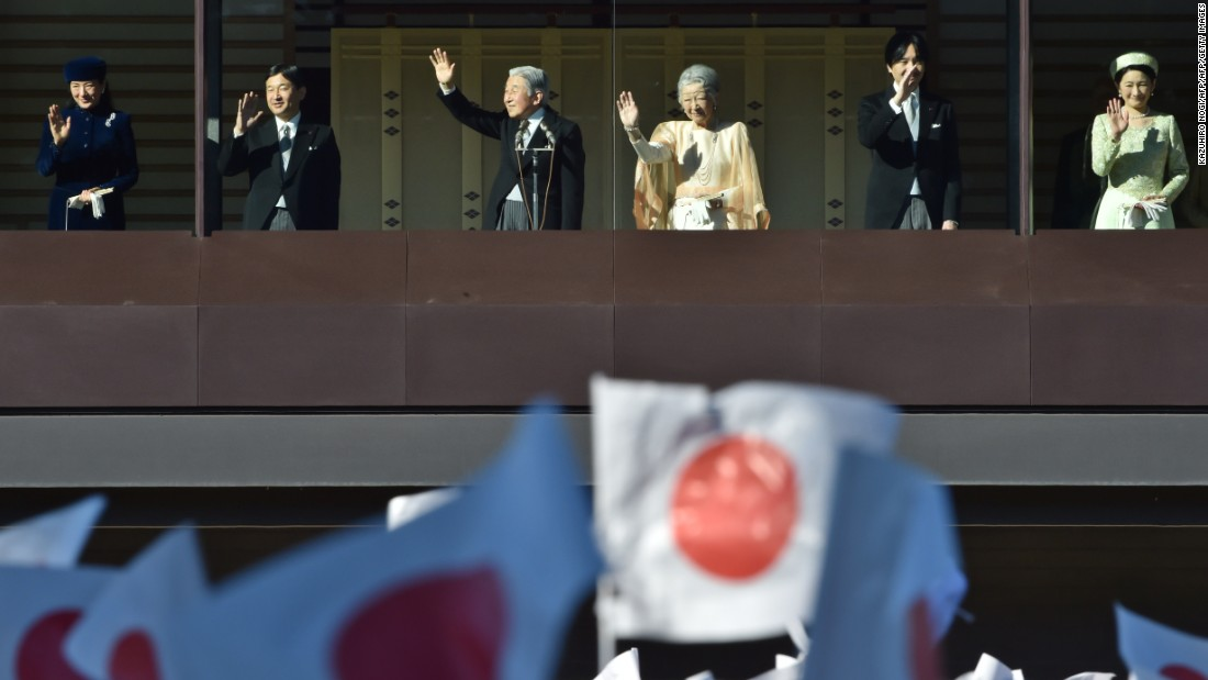 From the balcony of the Imperial Palace, Emperor Akihito greets thousands of people, waving Japanese flags, who have gathered to wish him a happy 82nd birthday on December 23, 2014.
