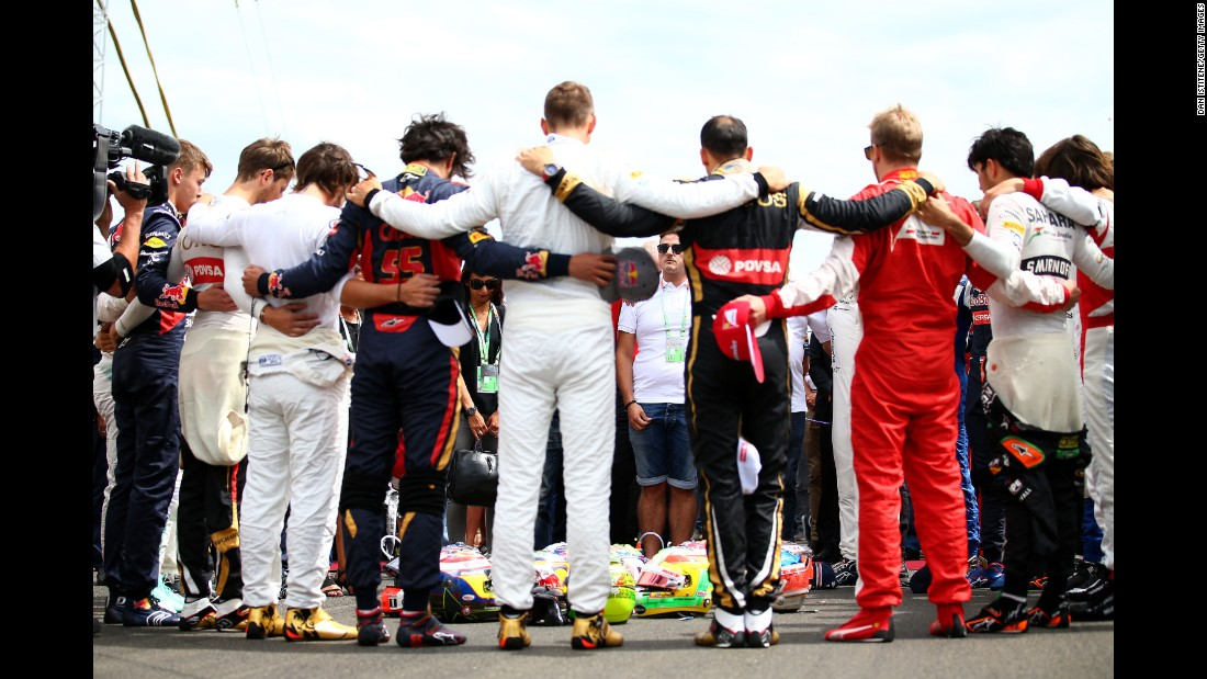 The Bianchi family and fellow drivers observe a minute's silence as they form a huddle around their helmets, including the late Bianchi's, before the start of the Hungarian GP at the Hungaroring on July 26, 2015 in Budapest, Hungary.
